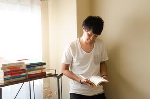 部屋で本を読む男性の素材 [FYI01078113]
