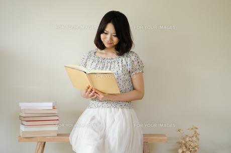 ベンチに座って本を読んでいる女性の素材 [FYI01078120]