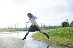 水たまりをジャンプする女子学生の素材 [FYI01078121]