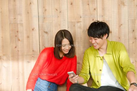 スマホを見ながら笑うカップルの素材 [FYI01078122]