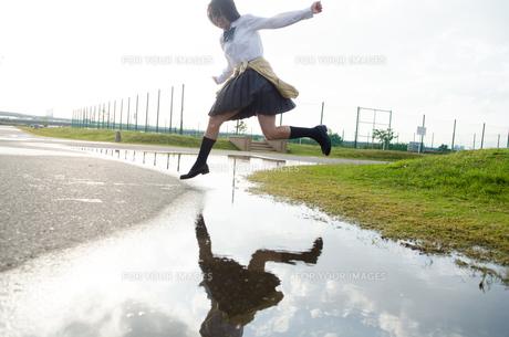 水たまりをジャンプする女子学生の素材 [FYI01078130]