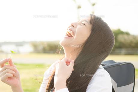 クローバーを持って笑う女子学生の素材 [FYI01078131]