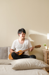 ベッドの上でギターを弾く男性の素材 [FYI01078138]