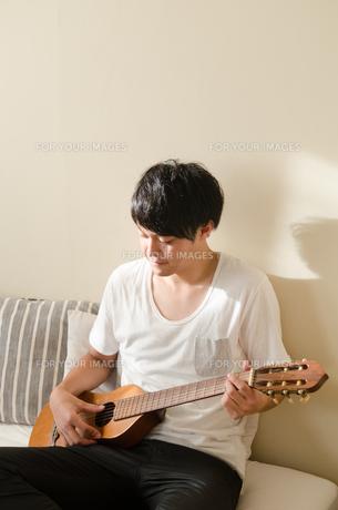 ベッドの上でギターを弾く男性の素材 [FYI01078149]