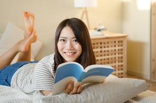 ベッドで本を読んでいる笑顔の女性の素材 [FYI01078150]