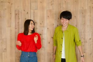 壁の前で笑うカップルの素材 [FYI01078151]