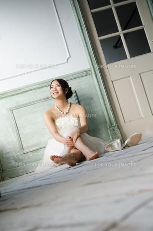 白いドレスを着て床に座る女性の素材 [FYI01078156]