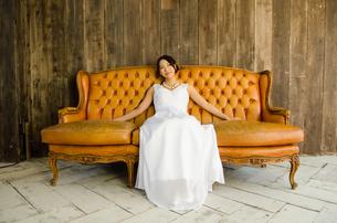 大きなソファに座るドレス姿の女性の素材 [FYI01078165]