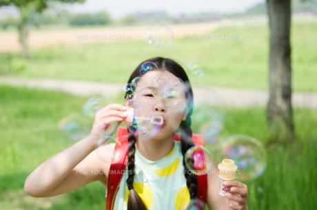 ランドセルを背負ってシャボン玉を吹いている女の子の素材 [FYI01078167]