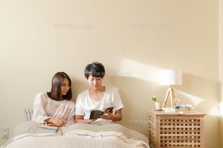 ベッドの上で本を読むカップルの素材 [FYI01078168]