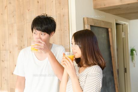 オレンジジュースを飲むカップルの素材 [FYI01078170]