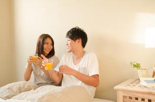 ベッドでオレンジジュースを持っているカップルの素材 [FYI01078171]