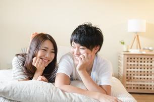 ベッドの上で笑うカップルの素材 [FYI01078172]