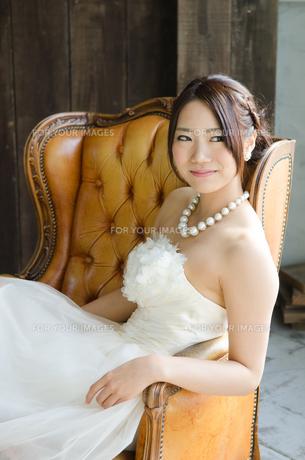 白いドレスを着てソファに座る女性の素材 [FYI01078178]