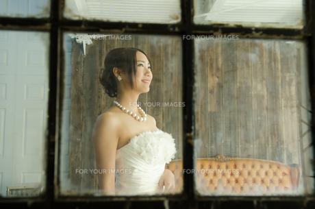 窓越しに見えるドレス姿の女性の素材 [FYI01078183]