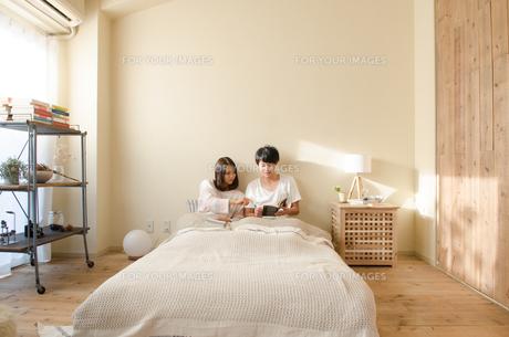 ベッドの上で本を読むカップルの素材 [FYI01078184]