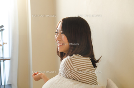 ベッドで笑う女性の素材 [FYI01078186]