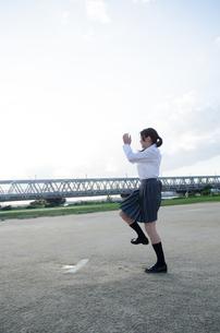ボールを投げるふりをする女子学生の素材 [FYI01078192]