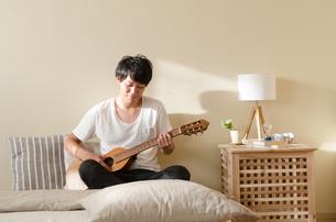 ベッドの上でギターを弾く男性の素材 [FYI01078200]