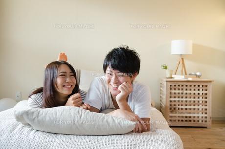 ベッドの上で笑うカップルの素材 [FYI01078202]
