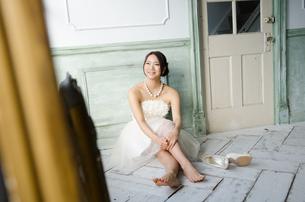 白いドレスを着て床に座る女性の素材 [FYI01078204]