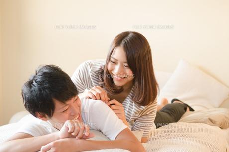 ベッドの上で笑うカップルの素材 [FYI01078206]