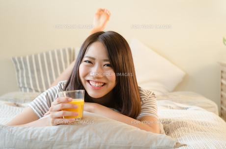 オレンジジュースを持って笑っている女性の素材 [FYI01078210]