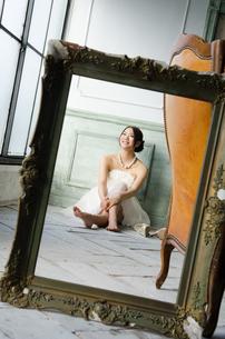 白いドレスを着て床に座る額縁越しの女性の素材 [FYI01078213]