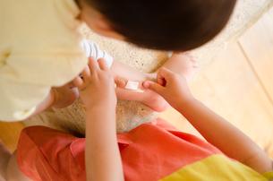 小さな子に絆創膏を貼っている女の子の手の素材 [FYI01078218]