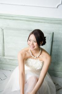 白いドレスを着て床に座る女性の素材 [FYI01078219]