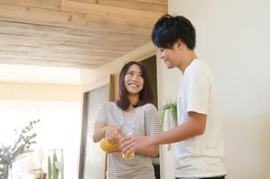 オレンジジュースをつぐカップルの素材 [FYI01078220]