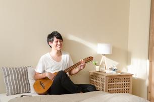 ベッドの上でギターを弾く男性の素材 [FYI01078228]