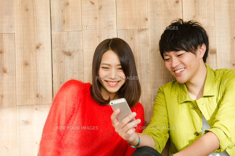 スマホを見ながら笑うカップルの素材 [FYI01078234]