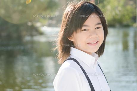 光の中で笑っている小学生の女の子の素材 [FYI01078236]