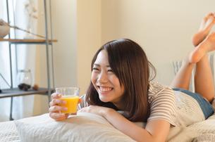 オレンジジュースを持って笑っている女性の素材 [FYI01078237]