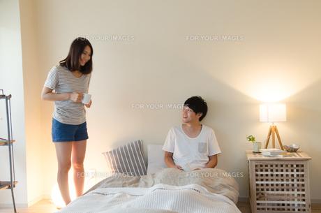 ベッドの側で笑うカップルの素材 [FYI01078246]