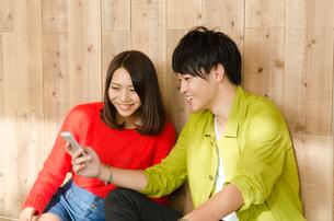 スマホを見ながら笑うカップルの素材 [FYI01078249]