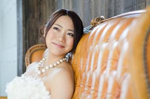 白いドレスを着てソファに座る女性の素材 [FYI01078251]