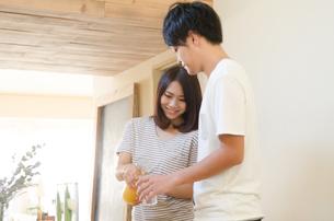 オレンジジュースをつぐカップルの素材 [FYI01078254]