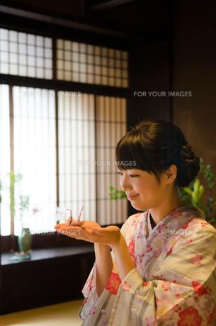 手のひらに折り鶴を乗せた着物姿の女性の素材 [FYI01078261]