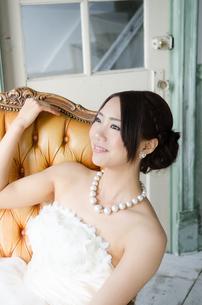 白いドレスを着てソファに座る女性の素材 [FYI01078265]