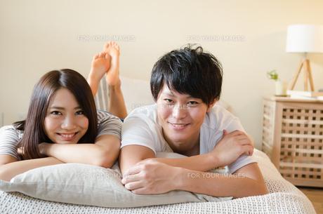 ベッドの上で笑うカップルの素材 [FYI01078269]