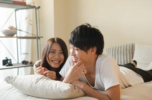 ベッドの上で笑うカップルの素材 [FYI01078271]