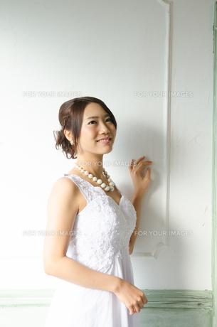 壁に手をかけるドレス姿の女性の素材 [FYI01078272]