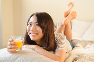 オレンジジュースを持って笑っている女性の素材 [FYI01078273]