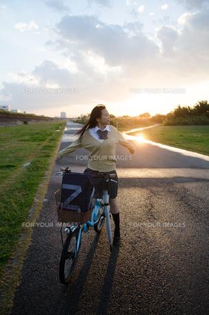自転車にまたがって深呼吸する女子学生の素材 [FYI01078284]