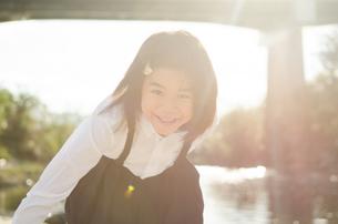 光の中で笑っている小学生の女の子の素材 [FYI01078290]