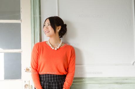 壁の前で笑う女性の素材 [FYI01078296]