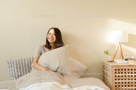 ベッドで枕を抱える女性の素材 [FYI01078300]
