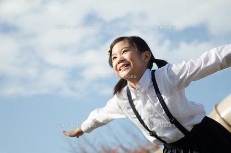 飛ぶポーズをしている小学生の女の子の素材 [FYI01078308]